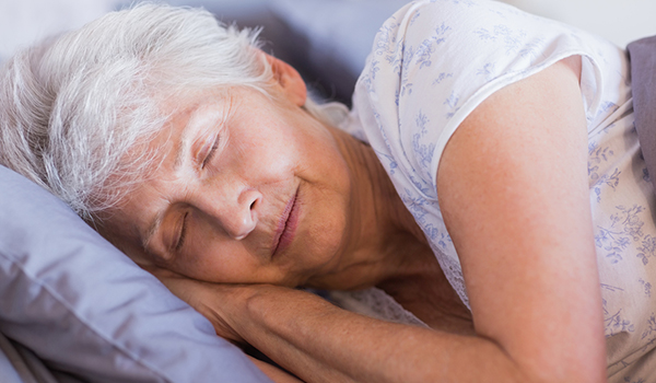 Mature woman sleeping in her bed