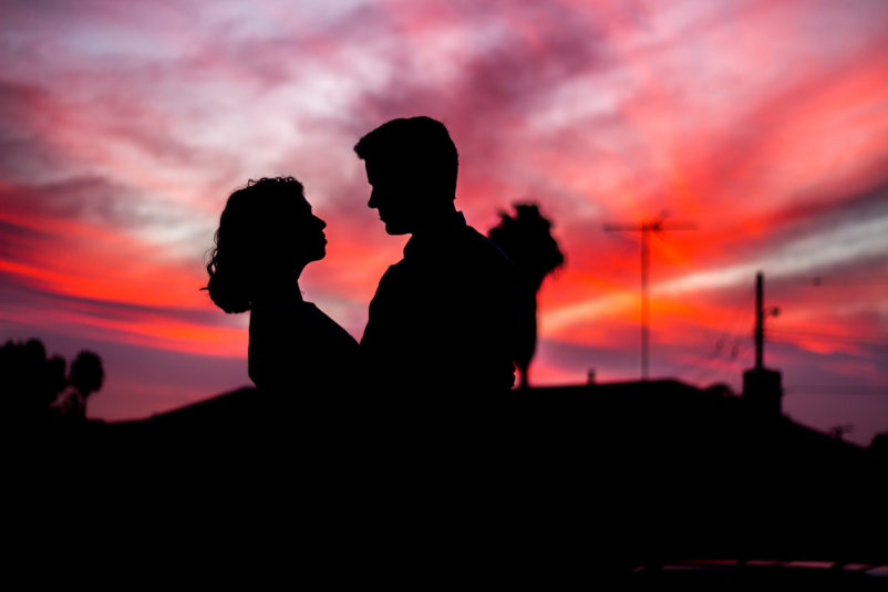 silhouette of couple looking at each other at sunset
