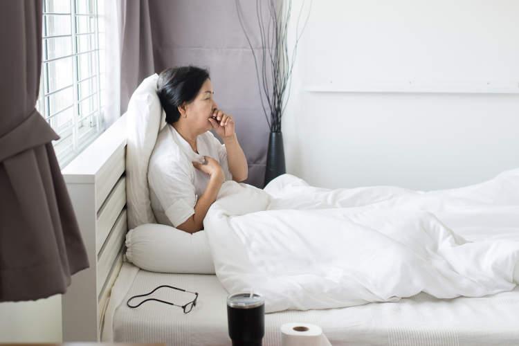 妇女在床上咳嗽