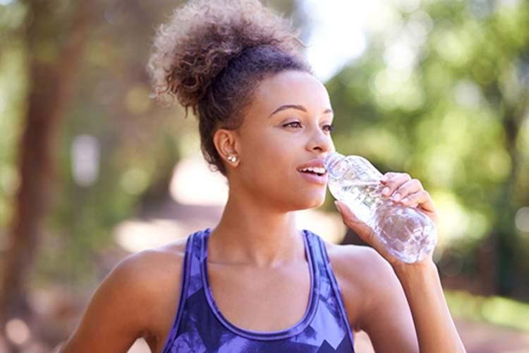 Woman drinking water while exercising.