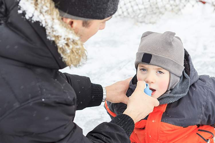 Dad helping young son with asthma use an inhaler outside in the winter.