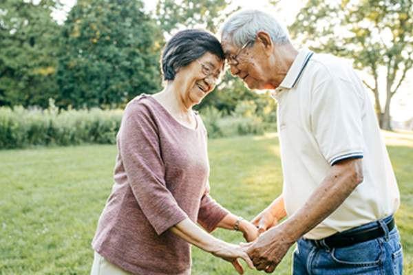 Senior couple holding hands outside in yard.