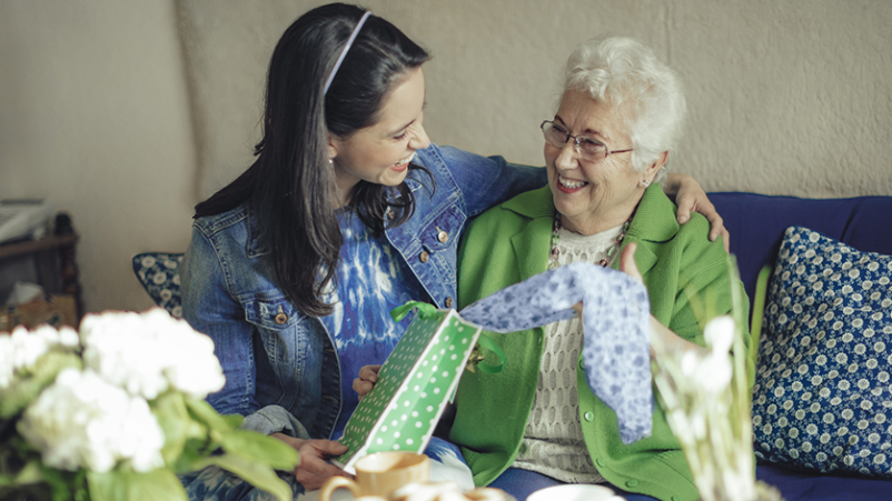 Senior woman giving gift to caregiver.