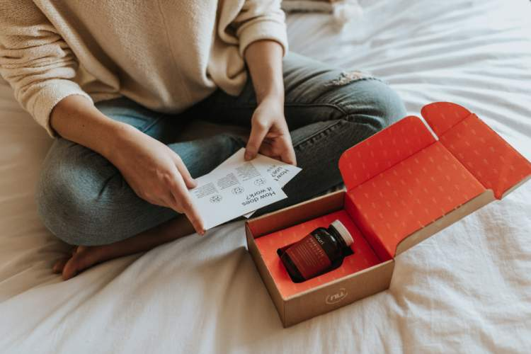 Woman sitting on bed while reading package materials included within a supplement subscription box