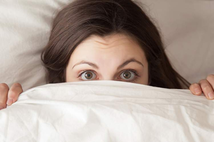 Embarrassed woman in bed peeking out from under the covers.