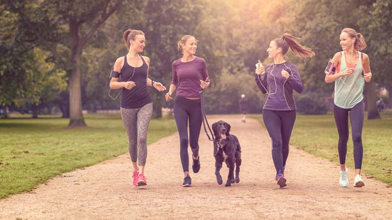 Three women exercising and walking a dog in a park.