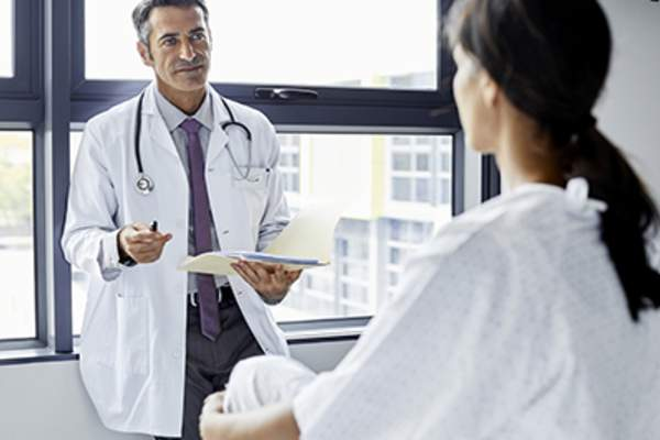 Young woman talking to doctor.