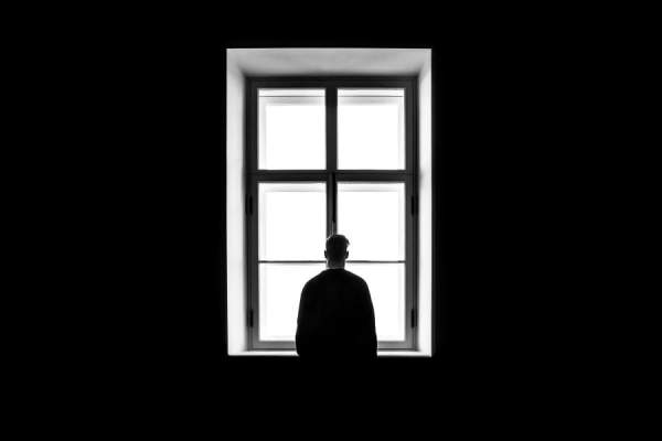 silhouette of man alone staring out window