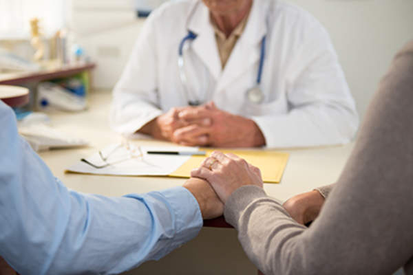 Couple holding hands at a doctor appointment.