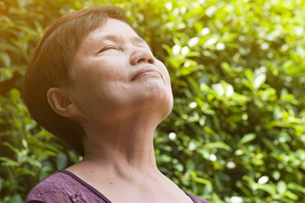 Asian senior woman relaxing and breathing fresh air