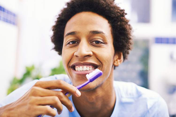 Smiling man brushing his teeth image.