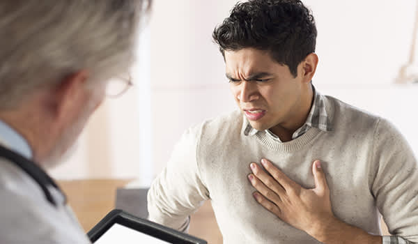 Man with acid reflux describing his symptoms to a doctor.