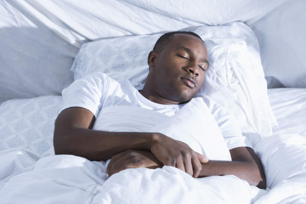 Young African American man asleep on back in bed.