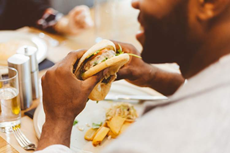 African American man eating a burger in a restaurant.