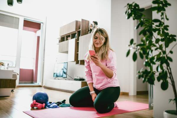 young woman looking at phone and using exercise equipment at home