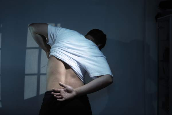 Man with back pain getting undressed at night.