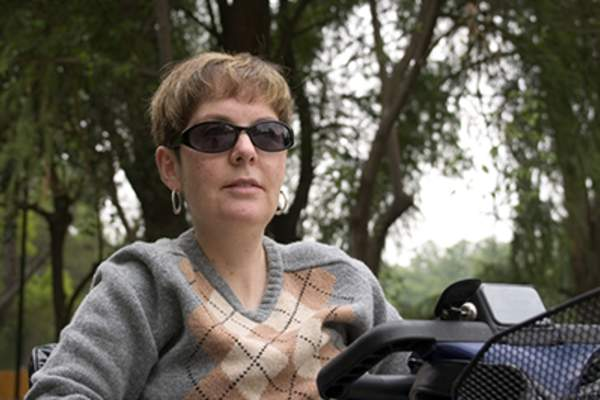 Woman wearing sunglasses and riding on a scooter in a park.