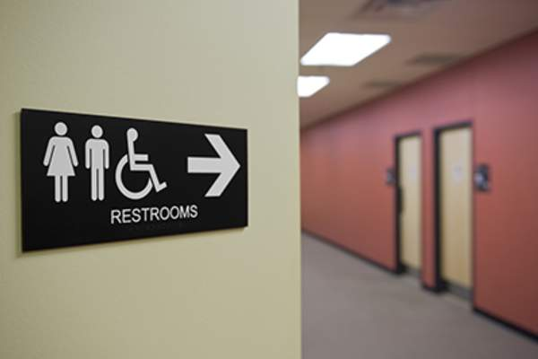 Restroom sign pointing to bathroom doors.