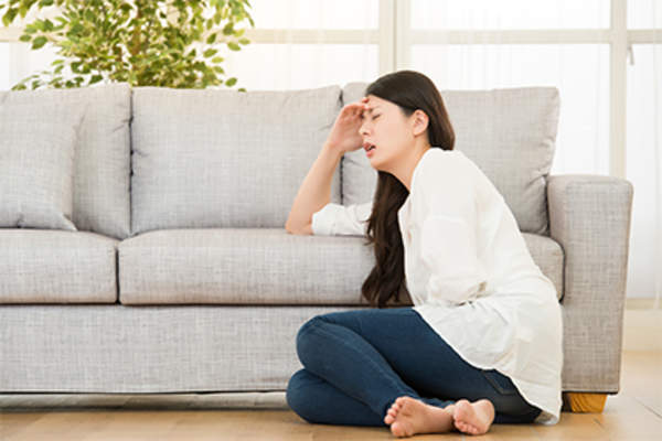 Woman with stomach pain sitting on the floor at home.