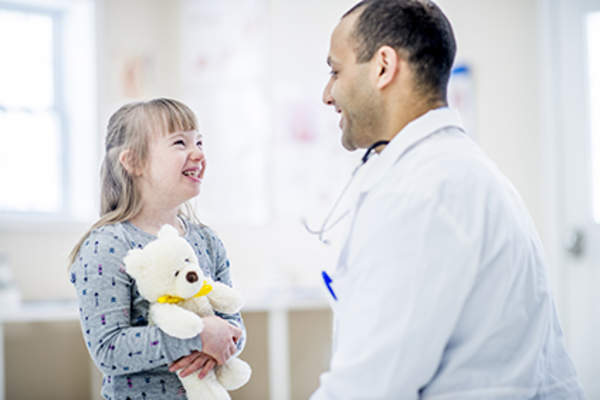 Child with Down syndrome with a doctor.