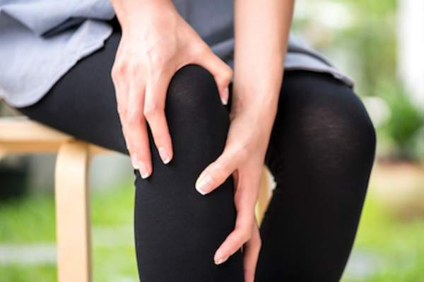 woman rubbing inflamed knee.