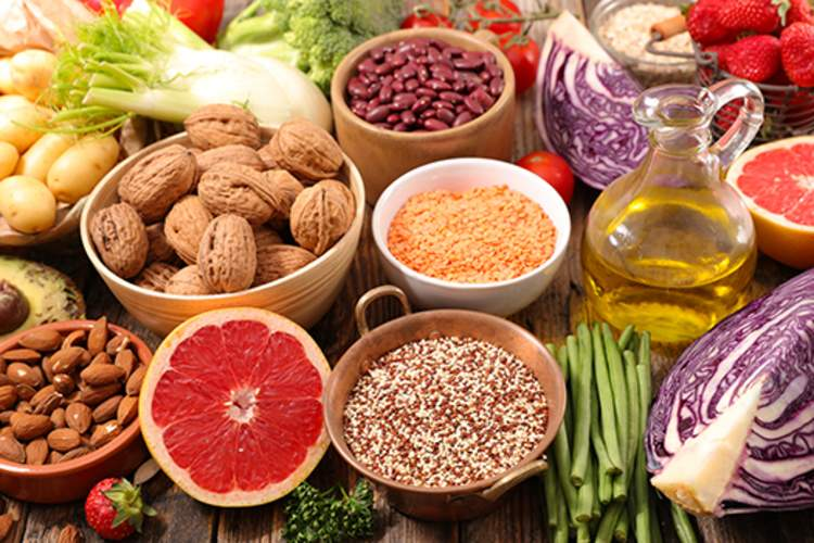 Assortment of healthy foods, including nuts, beans, and fresh vegetables.
