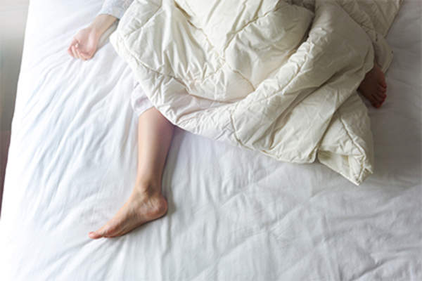 Woman's arm and leg under comforter in bed.