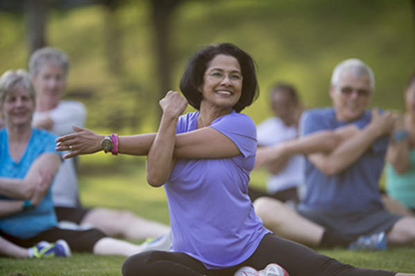 Middle age woman stretching in an outdoor exercise class.