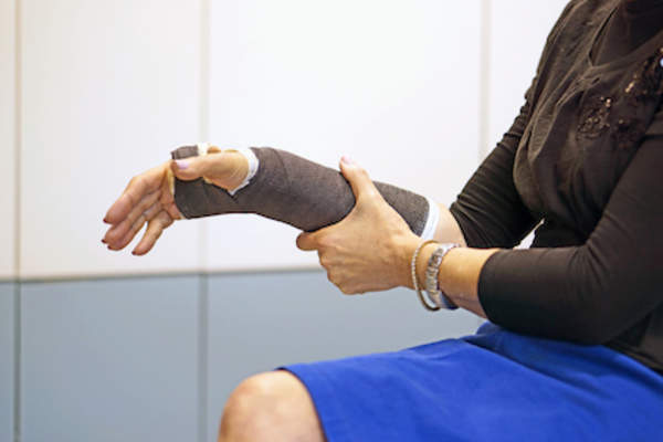 Woman with wrist in cast.