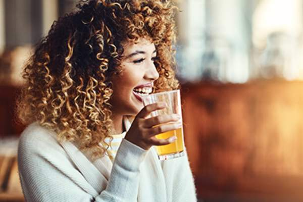Woman drinking beer while laughing.