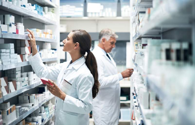 two pharmacists looking at shelves
