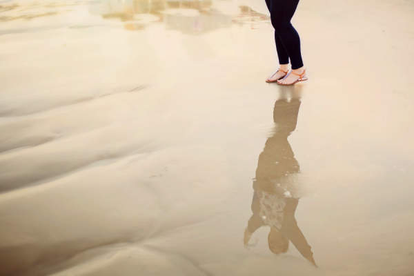 woman standing in water, arms raised in reflection