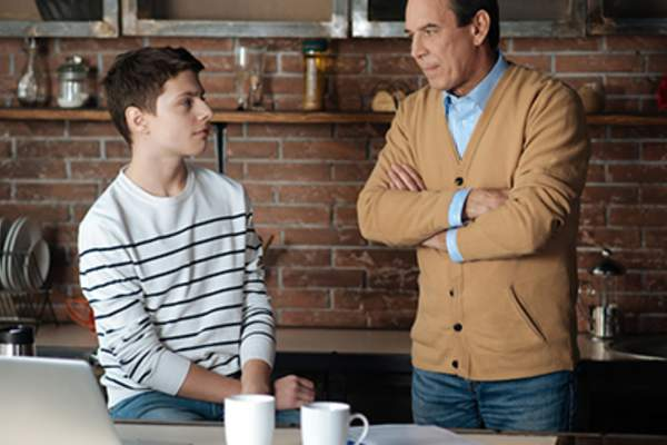 Father talking to teen son in kitchen with open laptop.