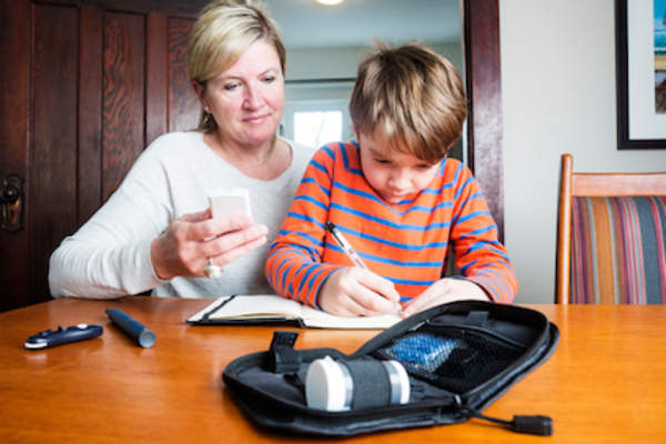 Mother helping diabetic child track blood sugar.
