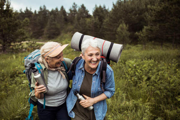 two senior female friends hiking together