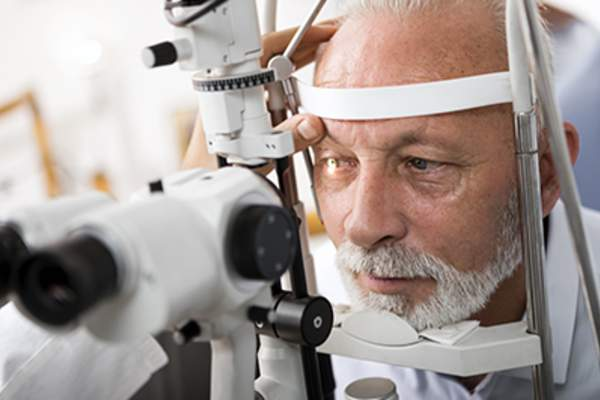Senior man getting an eye exam from an optometrist.