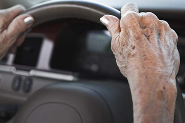 Senior woman hands with age spots on steering wheel