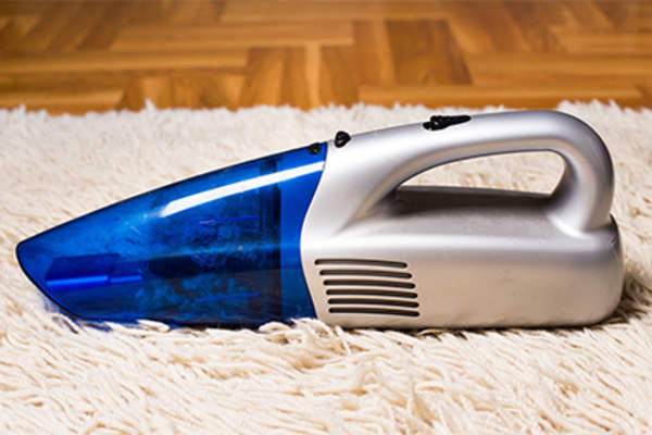 Handheld vacuum dustbuster on rug.