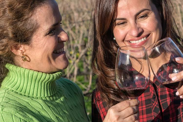 Smiling women drinking a glass of wine outside at a winery.