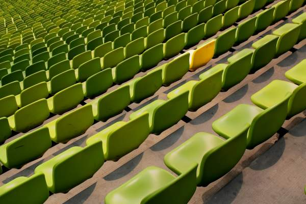 stadium full of green chairs, one chair is yellow
