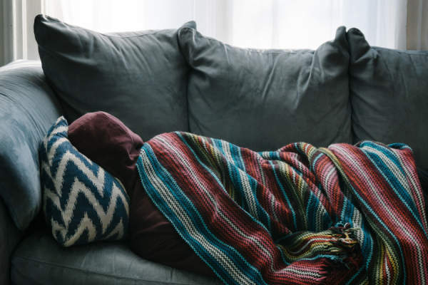man on a couch wrapped in blanket
