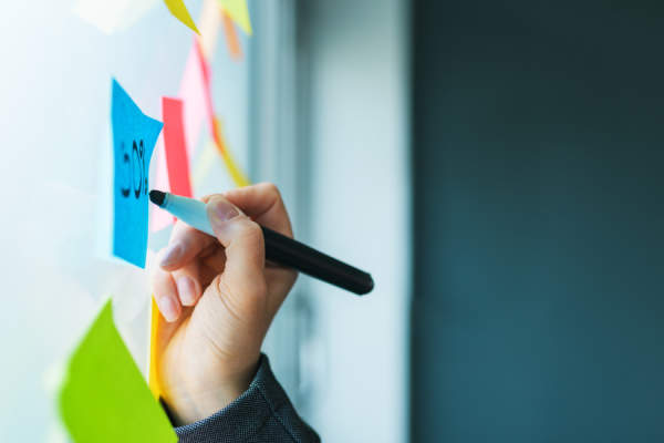 woman writing on colorful sticky note paper
