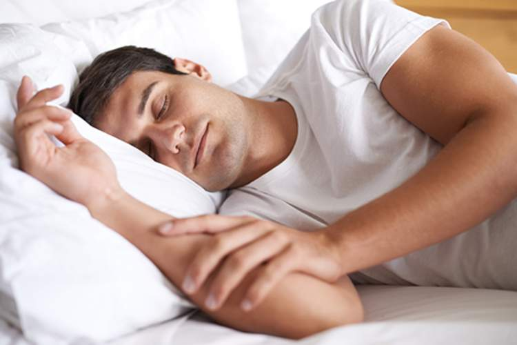 Man sleeping happily in bed.