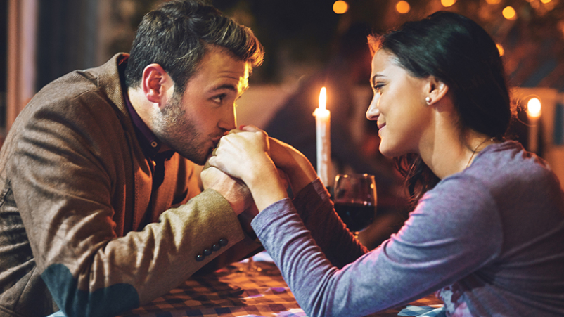 Man kissing woman's hand while on a date.