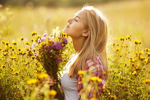 Woman smelling a field of flowers.