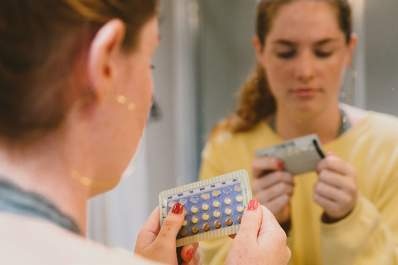 Woman looking at her sheet of birth control pills in a mirror.