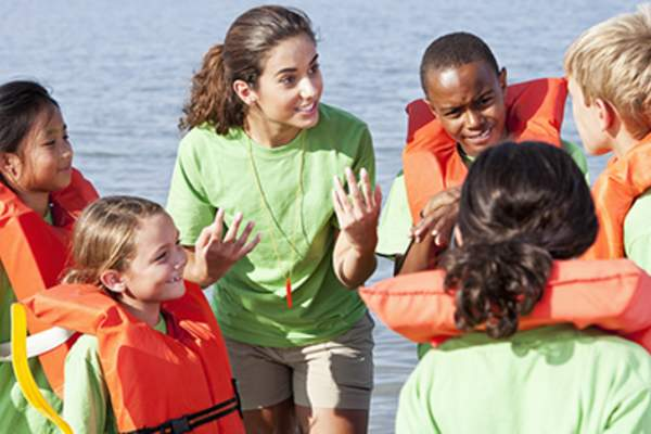 Summer camp counselor talking to children wearing life jackets.