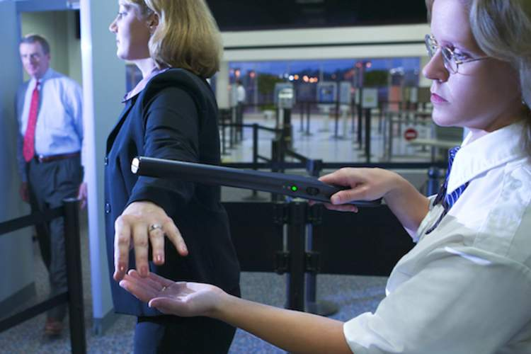 An airport traveler gets checked with a wand by TSA.