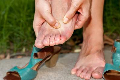 A woman with Morton's neuroma rubs her aching feet.