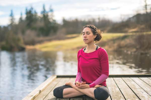 Woman meditating at lake on pier.